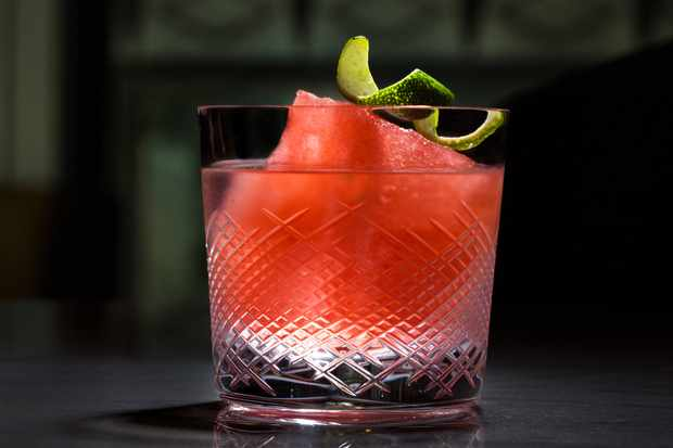 A glass filled with a pink vesca negroni with a garnish of lime on top
