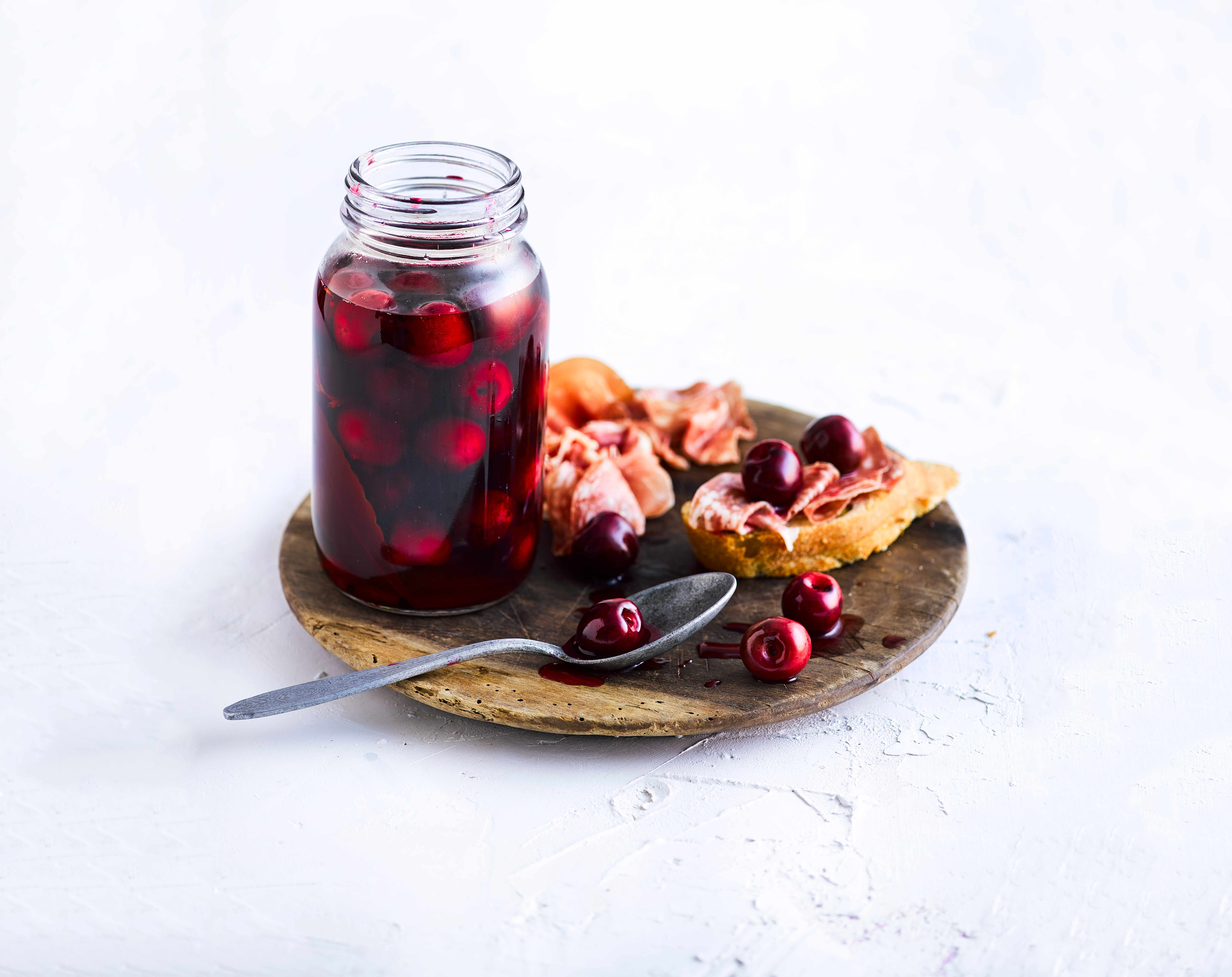 Pickled Cherries in a kilner jar served on a wooden board with ham and bread