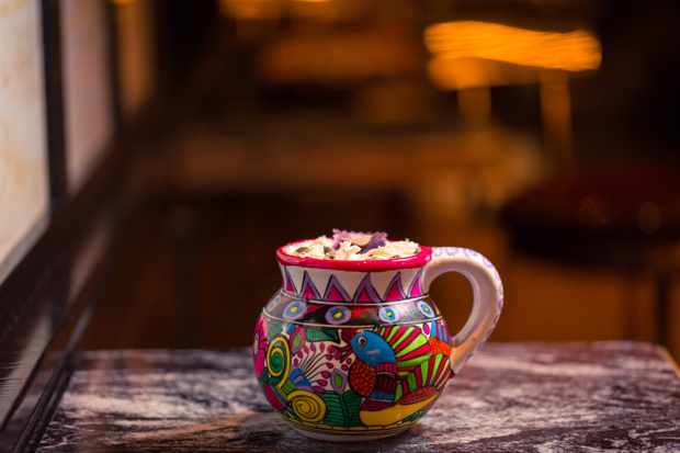A colourful painted mug filled with white frothy cocktail