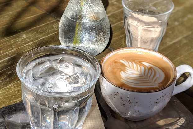 A small silver tray is topped with a flat white, a glass of water and a wafer biscuit