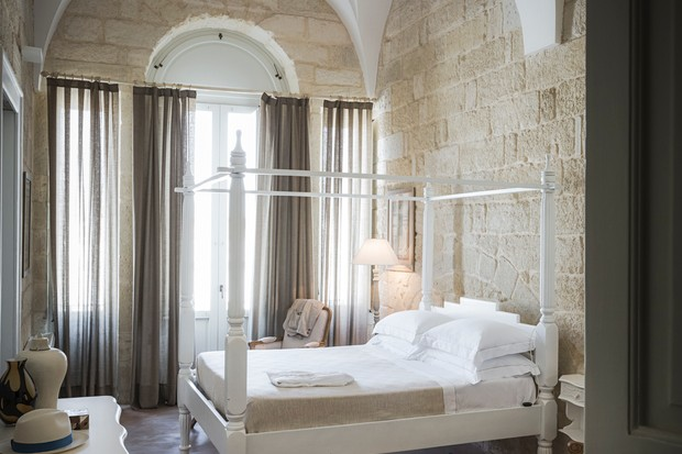A hotel room with a four poster bed and stone walls