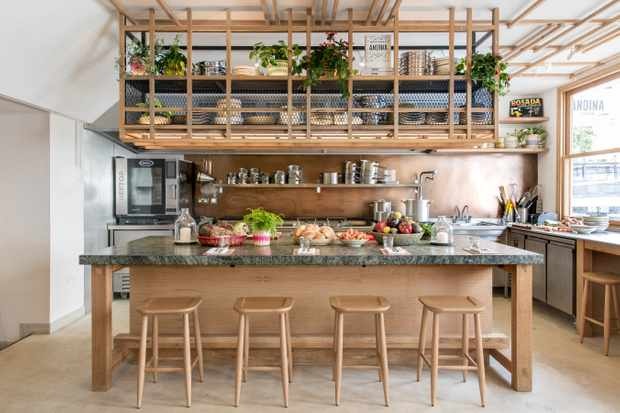 A wooden open kitchen counter with four bar stools