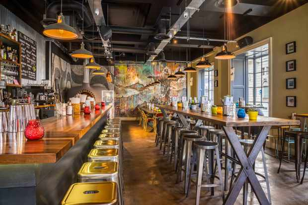 Interiors at Santa Maluco, Liverpool. A wall covered in a graffiti mural of Christ the Redeamer sits on the back wall, while metal bar stools surround communal wooden tables