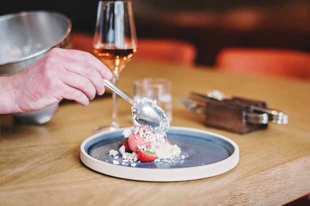 Strawberry dessert and glass of wine on wooden table
