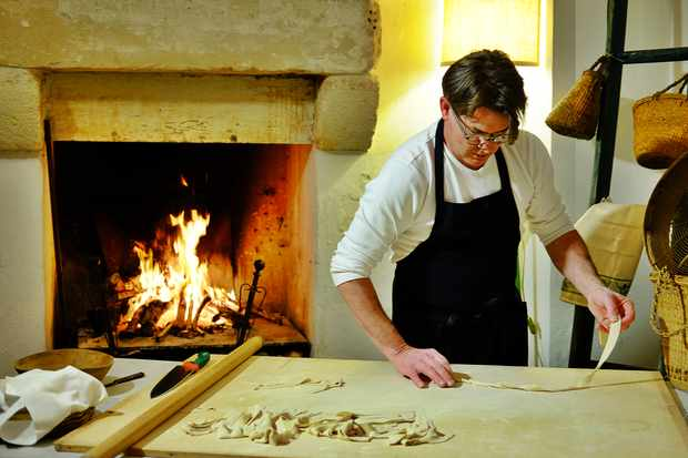 A chef in an apron rolling out pasta in front of a fire