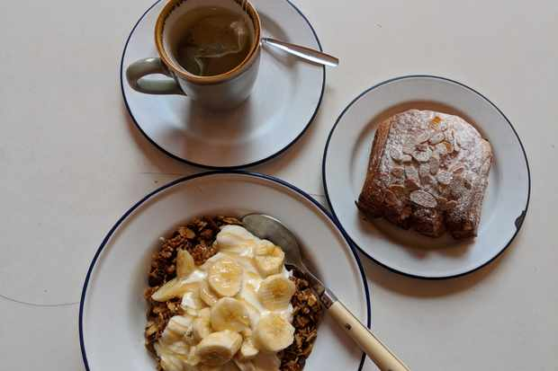 A white table is topped with 3 plates. On one is an almond croissant, another has a mug of mint tea on top and another is a bowl filled with granola, yogurt and slices of banana