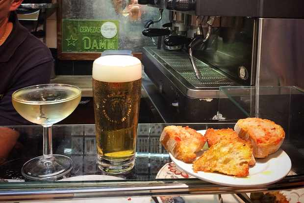 Glass of cava, small beer and bread on the counter at El Xampanyet Barcelona