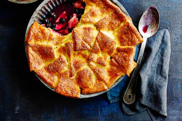 Apple and Blueberry Pie Recipe served in a metal pie dish and a large metal dessert spoon on a blue board