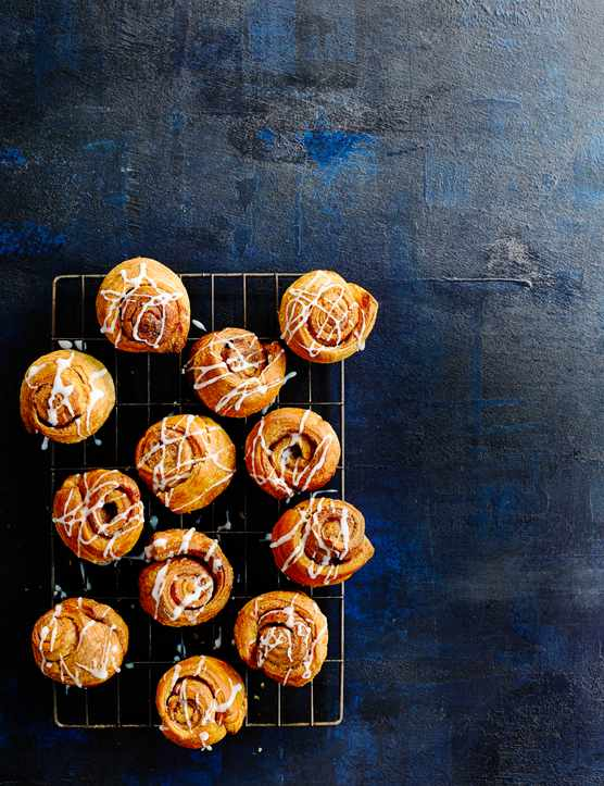 12 Croissant Cinnamon Rolls served on a cooling rack on z dark blue board