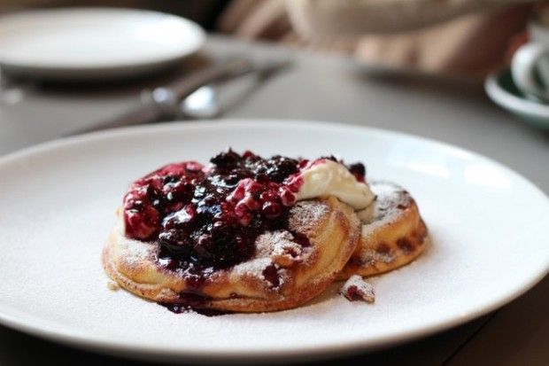 A white plate topped with two fluffy ricotta pancakes and drizzled with berry and liquorice compote and The Modern Pantry, Clerkenwell