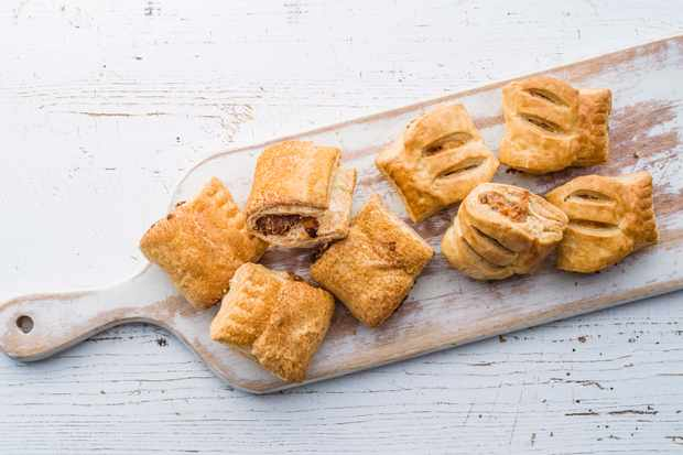 A long board topped with two types of sausage rolls