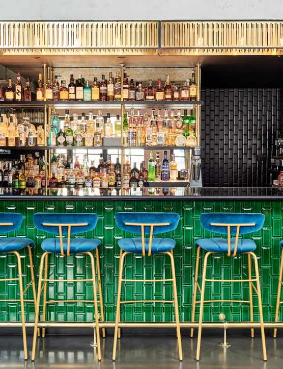 A bar with green tiles with blue chairs