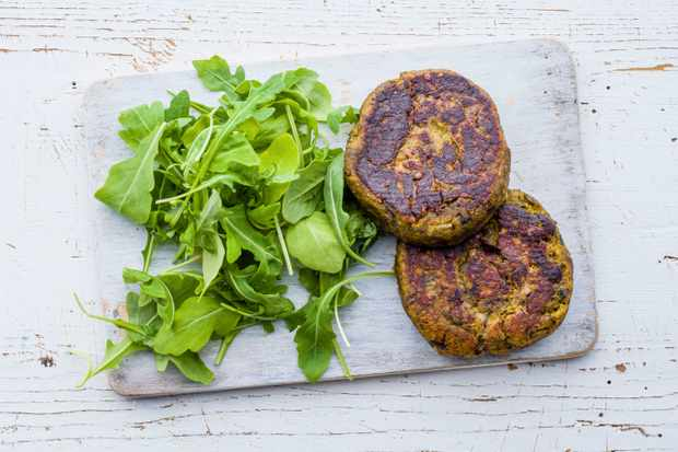 A grey board is topped with two spiced mushroom and cauliflower burgers and salad leaves