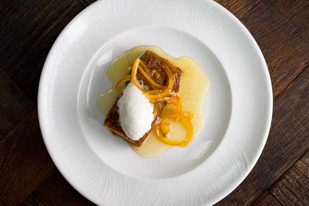 A white plate topped with a piece of marmalade sponge with a quenelle of ice cream on top and thin slithers of orange zest at Wreckfish bistro in Liverpool