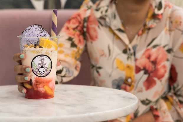 A girl in a floral shirt with a colourful ice cream shake