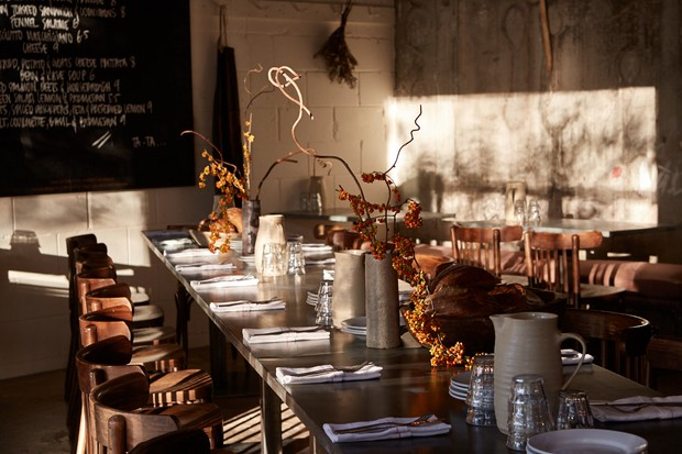 Interiors at Jolene, a long zinc table topped with ceramic vases filled with stems of flowers