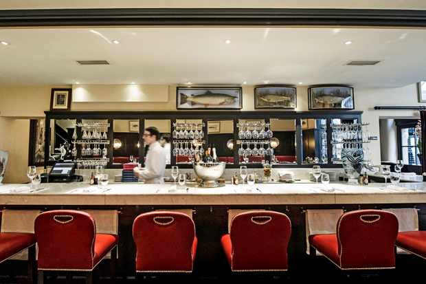 A white counter with red stools around the edge and and wine glasses hanging behind the bar