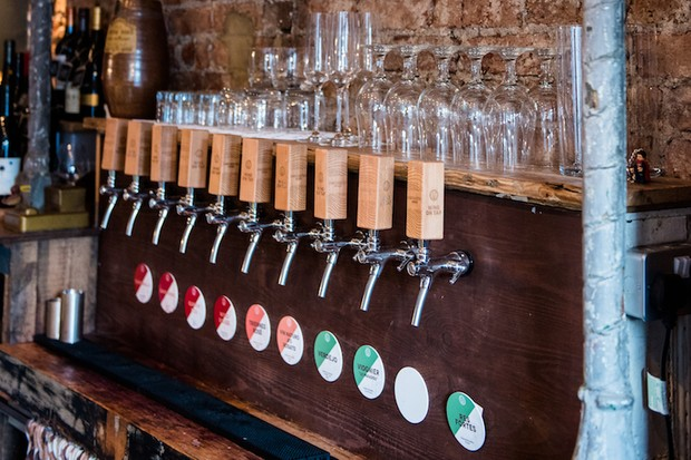 Wine taps against a brick wall at Tap and Bottle