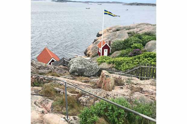 Red huts on rocky coast of Bohuslan Sweden