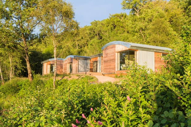 Wooden cabins are nestled amongst green fields