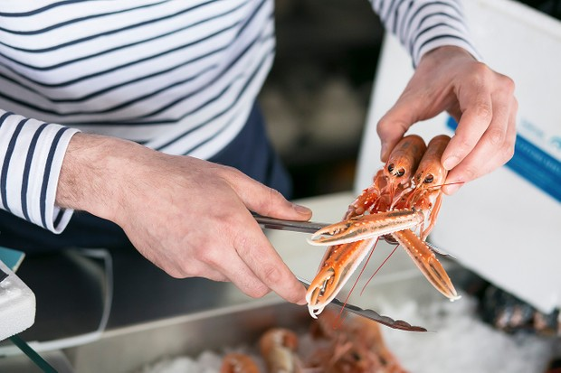 A lady opening a prawn at The Fishmarket Edinburgh