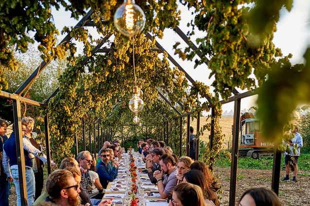 A long wooden table is laid in a field and people are sat on chairs ready to eat