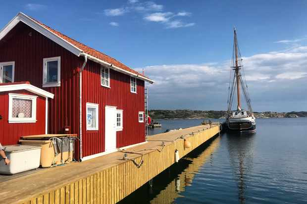 A fishing boat and red wooden house in Mollosund harbour, Sweden