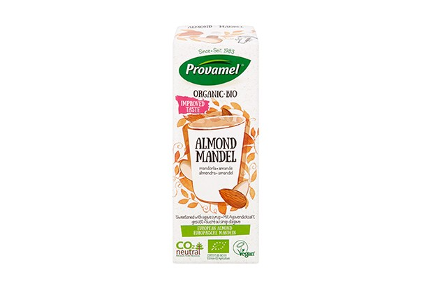 A white carton is filled with Provamel almond milk. There is a drawing on the front of a glass with almonds on it
