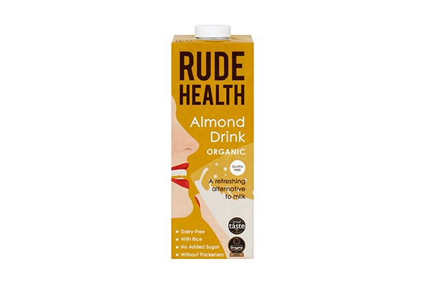 A dark yellow carton of Rude Health almond drink. There is a drawing on the front of a woman drinking a glass of the almond drink