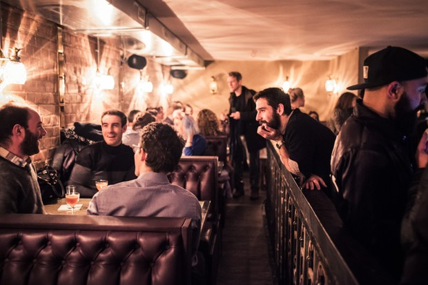 People sat in leather boots and people stood around the bar at Original Sin, Stoke Newington