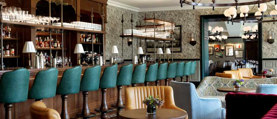 A striking bar with sea blue bar stools as well as leather armchairs and red velvet sofas