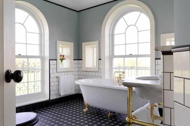 A marble tiled floor and pale blue walls in the bathroom at the University Arms hotel. There is a white freestanding bath in the window