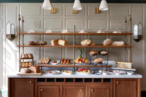 A large table with shelves is filled with bread, fruit, cheeses, meats, pastries, salmon and yogurt