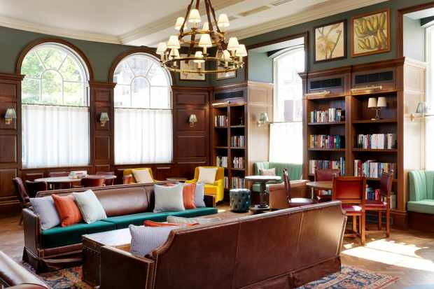 The library room at the University Arms hotel. Two brown leather sofas with cushions are in the centre of the room along with arm chairs and bookcases filled with books