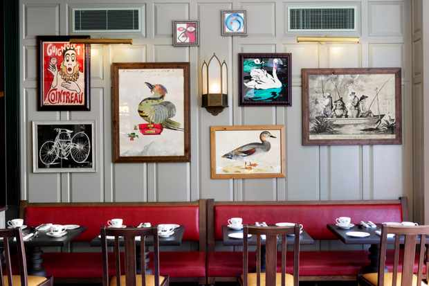 The dining room at the University Arms hotel. Red leather seats hug the pale grey washed walls which have Cambridge-inspired artwork hanging on them