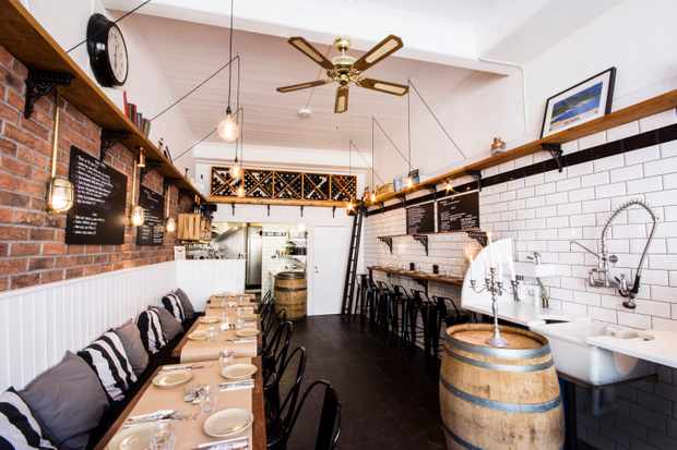 A dining room has white tiled walls and exposed brick work. There are long bench seats with cushions on as well as high stools