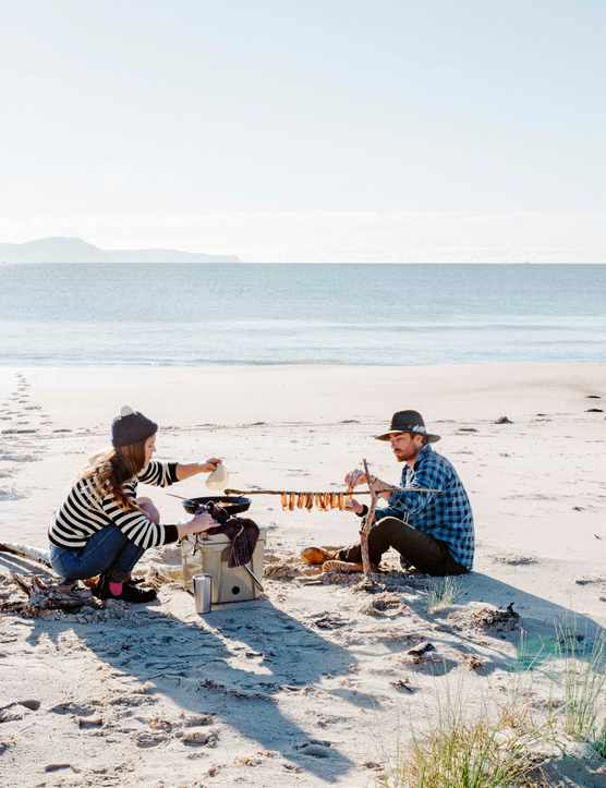 Two people drying fish on a beach in Tasmania