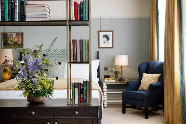 A large bedroom with pale blue walls, mustard yellow curtains and a blue armchair in the corner. There is a double bed and a book case with books and flowers on it