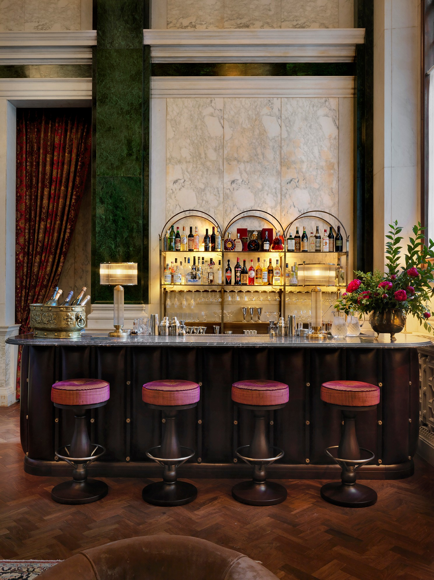A long, dark bar with pink stools and white walls