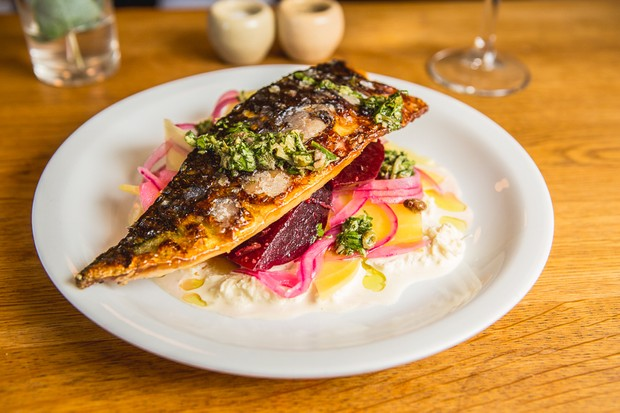 A white plate is topped with chunks of beetroot and a fillet of crispy fish with green sauce drizzled on top at Olyroyd restaurant in Islington