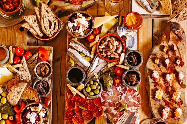 A wooden table is laden with wooden platters of cheese, charcuterie, olives and bread