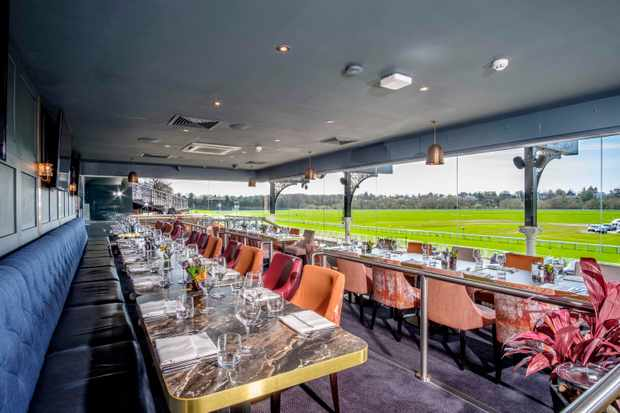 Tables and chairs are laid in a restaurant that looks out over a green racecourse