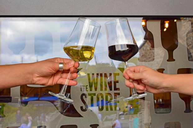 Two people are holding glasses. One is a glass of red and the other is a glass of white. The glasses are about to touch in the image and in the background is a glass door with 'The Wine Store' etched onto it