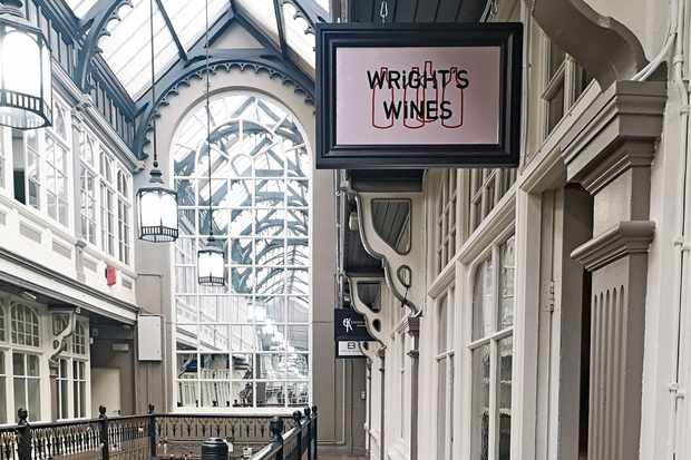 A Victorian-built shopping arcade is home to Wright's Wines. There is a small sign outside the shop which reads 'Wright's Wines' with line drawings of wine bottles in the background