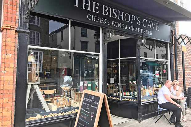 The outside of a cheese, wine and craft beer shop. There are glass windows filled with bottles of wines and a couple of seats on the pavement outside