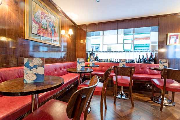 A wooden panelled room with red leather sofa seats and small circular wooden tables. There are bottles of wine lining the window sill