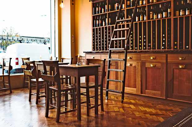 A wine bar has parquet flooring and wooden tables. There is a wooden unit filled with bottles of wine and a ladder leaning against the shelves