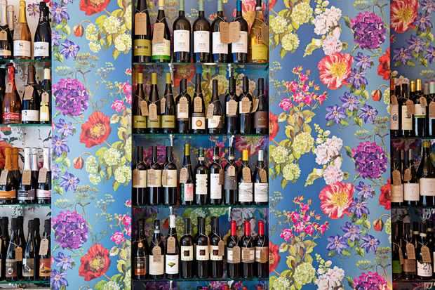 A colourful room has floral-patterned wallpaper. Between the wallpaper is a section with bottles of wine