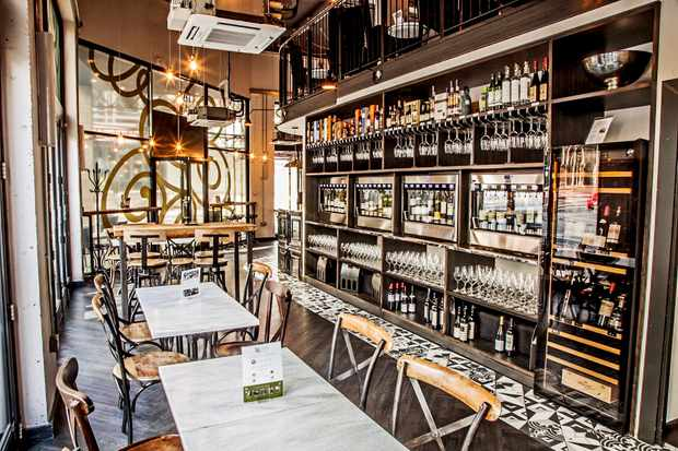 An open plan wine bar with marble tables and wooden chairs. There is a wall with shelving units full of bottles of wine