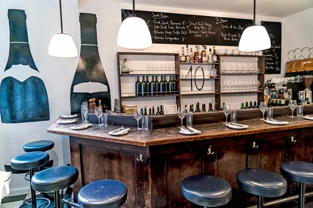 A restaurant has white walls with wine bottles painted onto them. There is a distressed wooden bar with blue leather high stools dotted around it. The bar is laid with napkins, cutlery and wine glasses